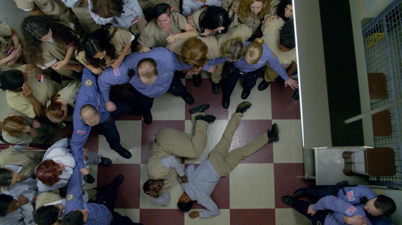 Poussey, morte, entourée des prisonnières de Litchfield