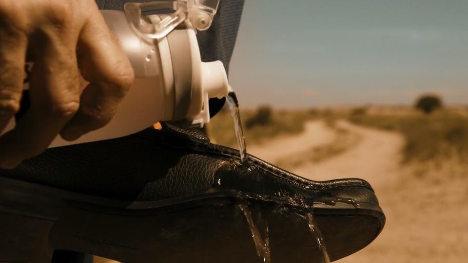 Gros plan sur la gourde de Saul versant de l'eau sur sa chaussure