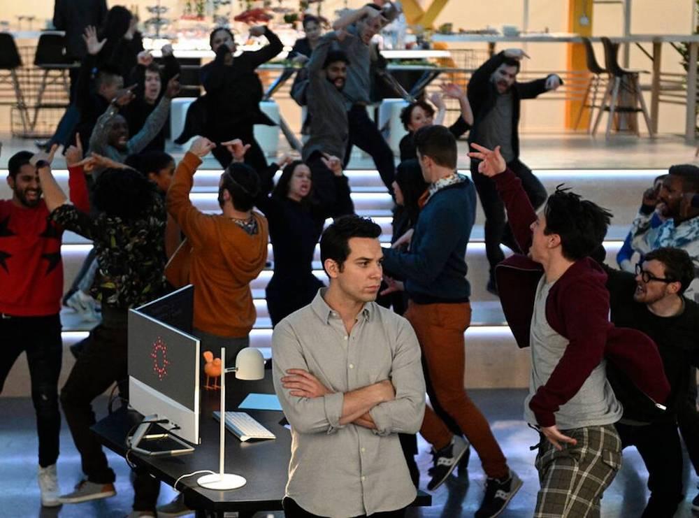 Max entouré par ses collègues qui chantent et dansent.