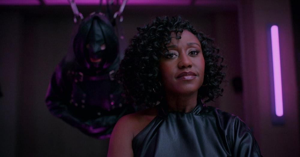 Image de Mira dans une salle du donjon avec un soumis en arrière-plan.