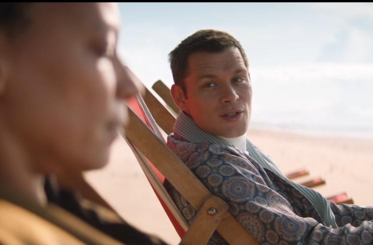 Elliot, sur la plage, en train de discuter avec la contrôleuse.