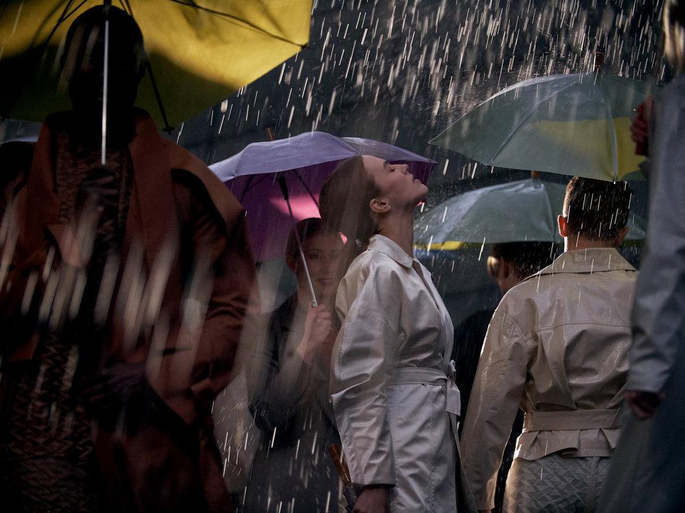 Lenina sous la pluie, appréciant sa douceur sans parapluie, entourée de gens avec des parapluies.