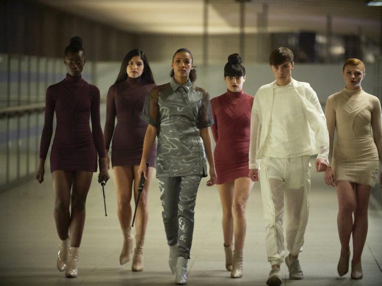Frannie marchant entourée d'autres personnages, probablement des Bêtas, un bâton électrique à la main.