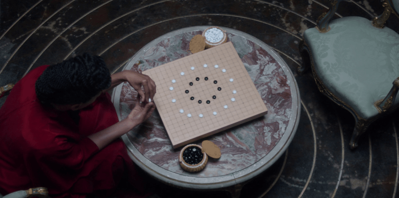 Mustapha Mond regarde le jeu des pierres noires et blanches disposées en cercles.