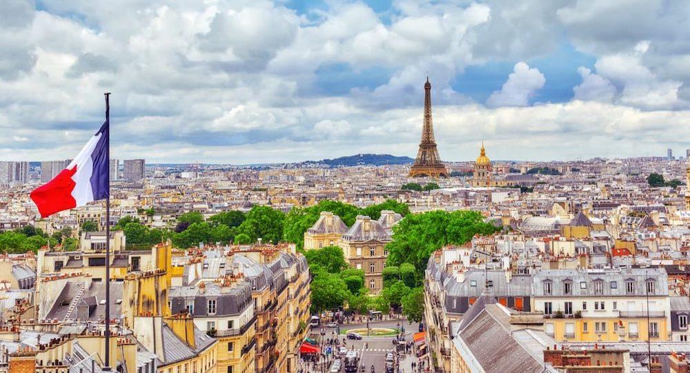Image de Paris : on voit au loin la Tour Eiffel et en premier plan un drapeau français.