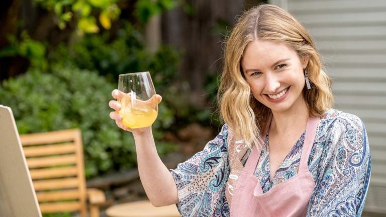 Madison, un verre à la main et souriante.