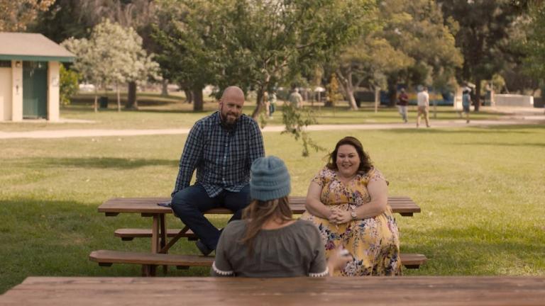 Toby et Kate sur une table de pique-nique faisant face à Ellie que nous voyons de dos.