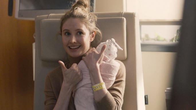Madison sourit et lève les pouces, un bébé dans les bras.